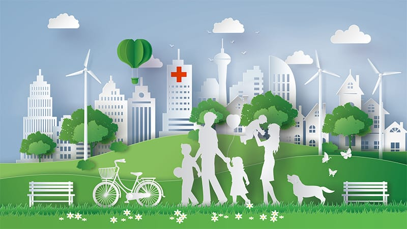 An illustration of a family in a park with wind turbines, a hospital, and a city skyline in the background.