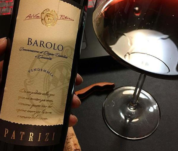 Bottle of Barolo DOCG by Patrizi 2017 held in a hand next to a glass of red wine.