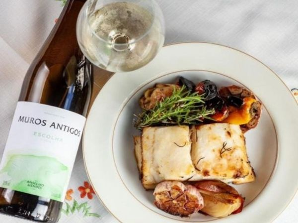 Bottle and glass of Muros Antigos Escolha Vinho Verde 2020 on a table next to a plate of fish and vegatables.