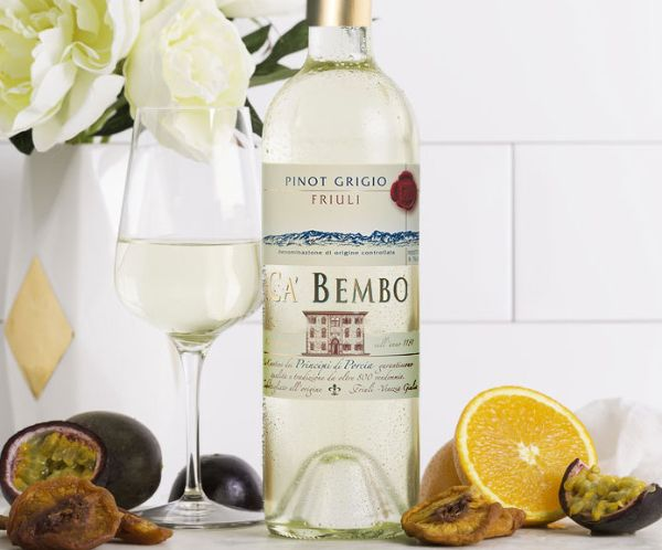 Bottle and glass of Ca Bembo Pinot Grigio Friuli Grave Doc 2020 on a table with cut lemon and cut figs.