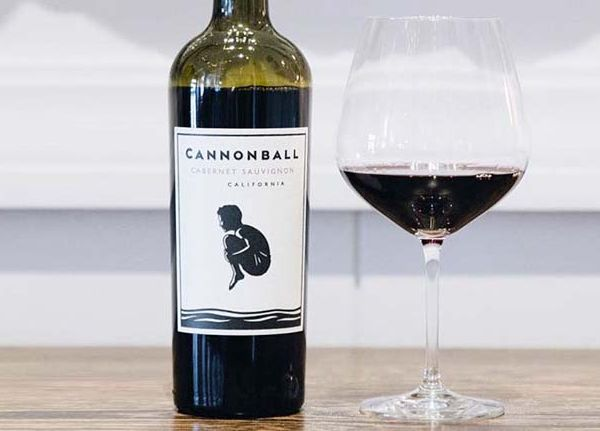 Bottle of Cabernet Sauvignon California by Cannonball 2018 showing the label next to a glass of red wine on a wooden table.