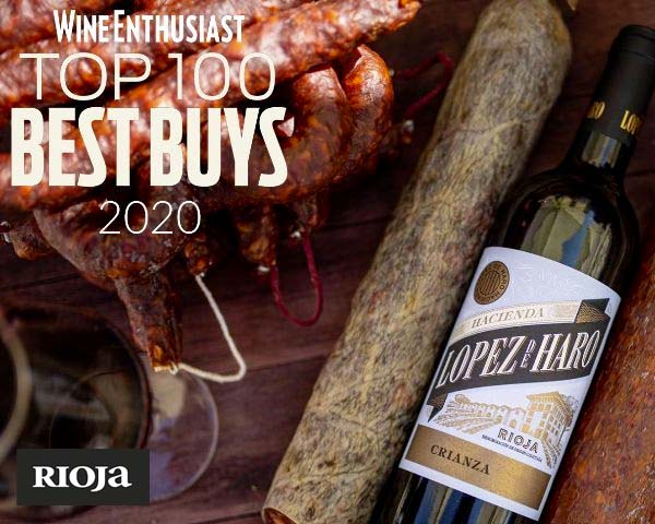 """Bottle of Lopez de Haro Crianza lying on a table next to a glass of wine and sausages ready to eat. Text reads, """"Wine Enthusiast. TOP 100 BEST BUYS 2020"""