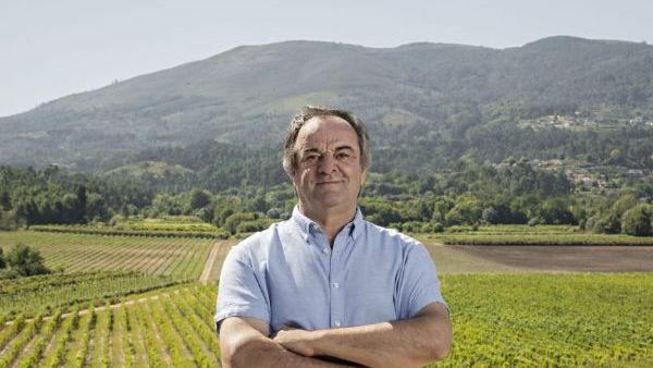 Anselmo Mendes, producer of Alvarinho Contacto Vinho Verde 2020, standing in the vineyard with a mountain range in the background.