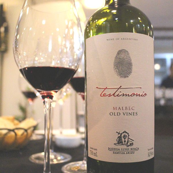Bottle of Testimonio Old Vines Malbec 2019 next to several glasses of red wine placed on a table.
