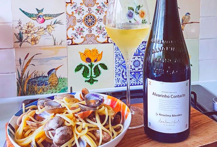 Bottle and glass of Alvarinho Contacto Vinho Verde 2020 on a table next to a enticing serving of linguine alle vongole