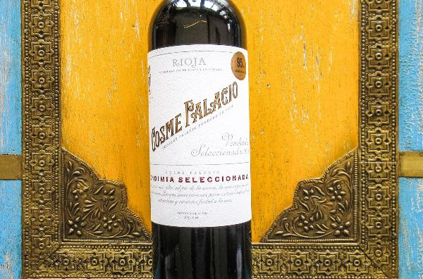 Bottle of Cosme Palacio Rioja Vendimia Seleccionada by Bodegas Palacio 2018 in front of a gold frame and yellow background.