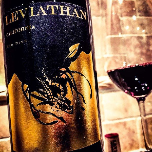 Close up of label of California Red Blend by Leviathan Wine 2018 and glass of wine against a brick background.