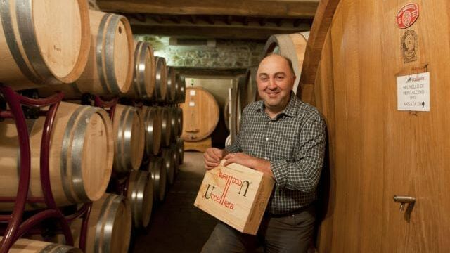 Andrea Cortonesi, winemaker of Uccelliera's Brunello Di Montalcino Riserva DOCG 2015 in the wine cellar among oak barrels holding an Original Wooden Case of wine.