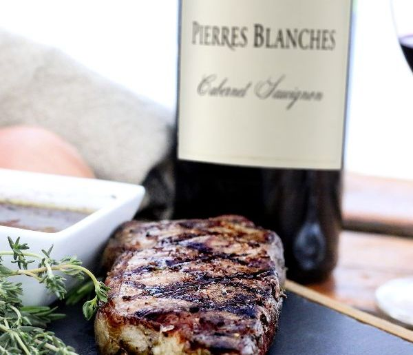 Cooked steak with hash marks in front of a bottle of Pierres Blanches Cabernet Sauvignon 2020.