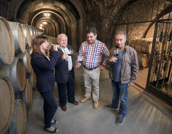 Four members of Bodegas Ismael Arroyo, producer of Valsotilla Finca Buenavista 2017 tasting wine in the cellar surrounded by oak barrels.