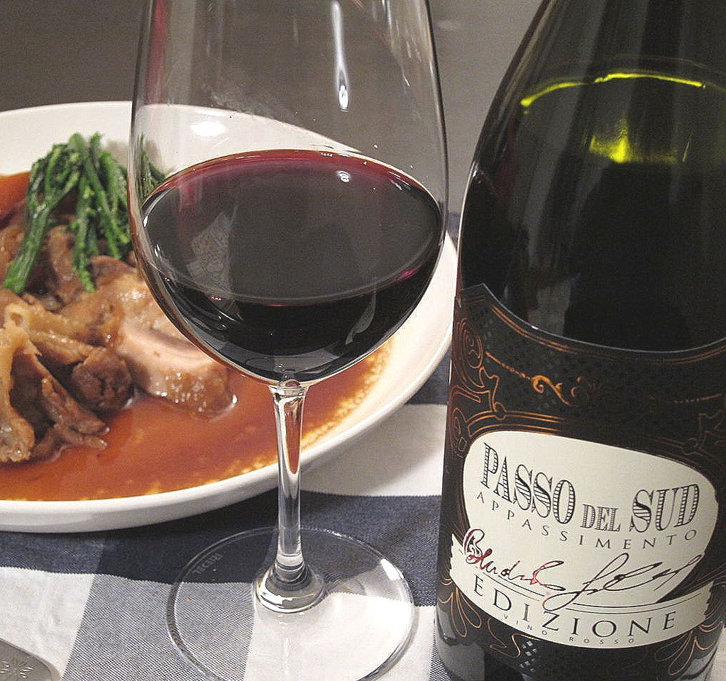 Bottle of Passo del Sud Edizione Appassimento 2018 beside a glass of red wine on a table covered with a black and white tablecloth in front of a plate with meat and gravy.