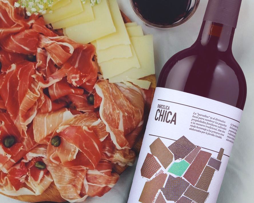 Bottle of Parcelica Chica Yecla by Bodegas Antonio Candela 2019 lying on a table next to a plate of sliced dried meat and cheese.