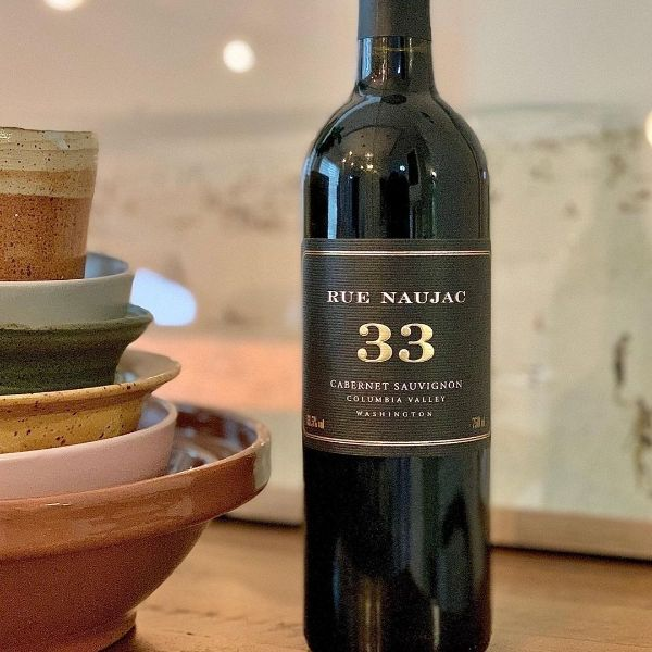 Bottle of Naujac 33 Cabernet Sauvignon Columbia Valley 2018 by Nicholas Pearce upright on a table next to coloured stacked bowls