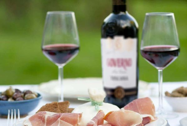 Bottle of Governo Igt Toscana Rosso by Barbanera 2019 on a white table in the background with 2 glasses of red wine in the foreground next to a plate of prosciutto and a bowl of olives.