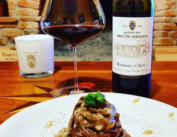 A bottle of Barbera D'Asti DOCG By Poderi Dei Bricchi Astigiani 2019 on a wooden table next to a glass of wine behind a plate of succulent pasta.