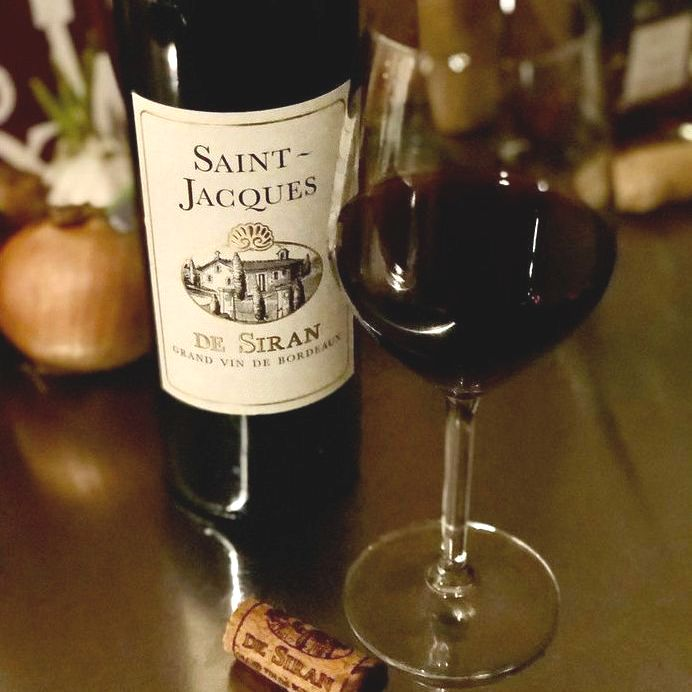 Bottle and glass of Saint-Jacques De Siran Bordeaux Superieur by Château Siran 2017 on a table.