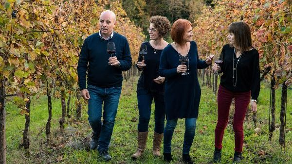 The Barbanera family, producers of Governo Igt Toscana Rosso 2019, walking through the vineyard holding glasses of red wine.