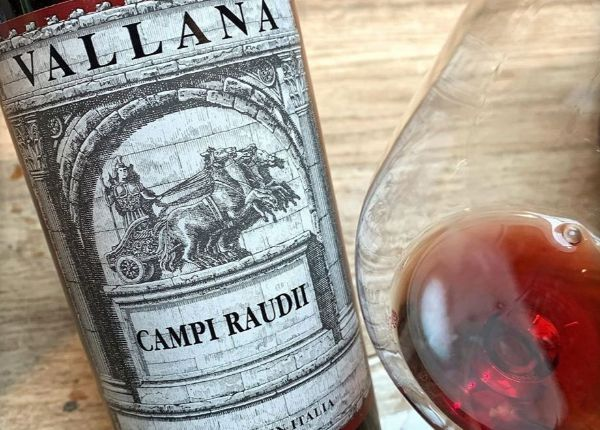 Bottle of Campi Raudii Lot 2010 displyed next to a glass of wine.