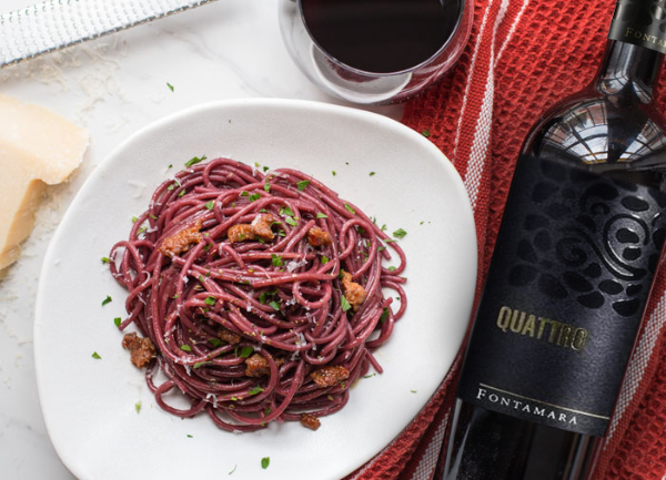 Bottle of Quattro by Fontamara 2018 next to a plate of red coloured spagetti on a white plate. Succulent visual.