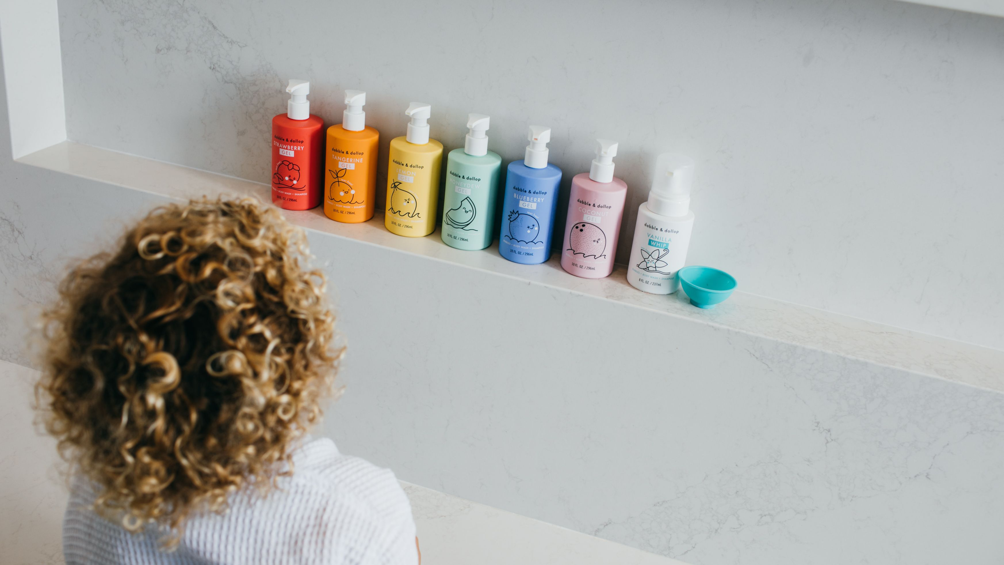 child with curly hair looking at lineup of shampoo bottles in multiple colors
