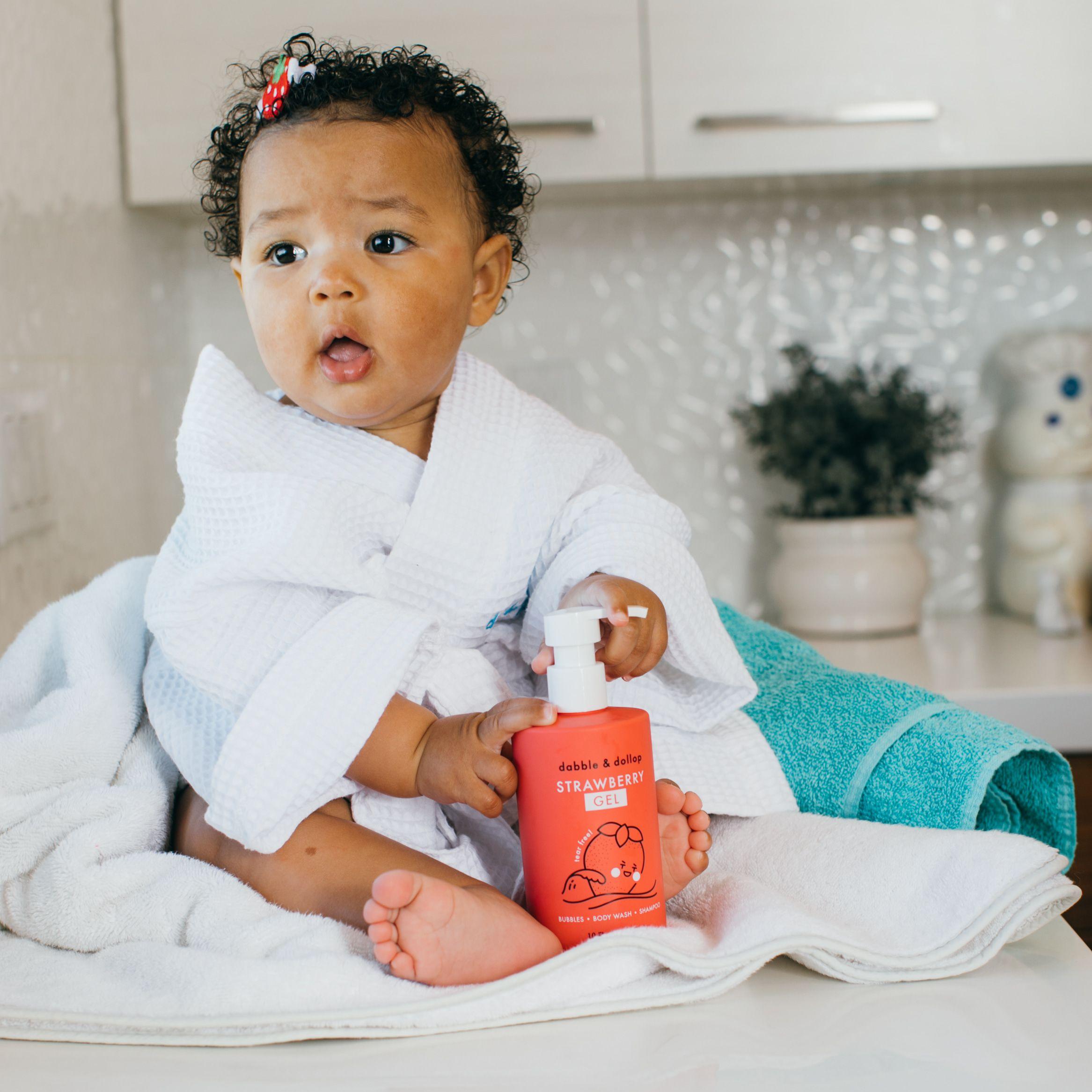Toddler in white robe holding bottle of strawberry shampoo