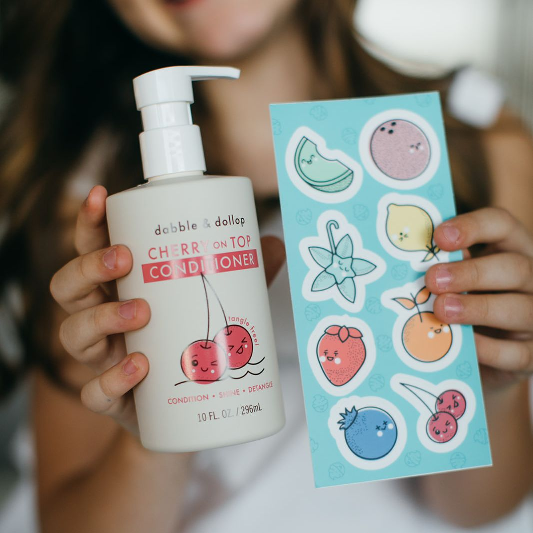 Child holding bottle of cherry conditioner and multi-fruit sticker sheet