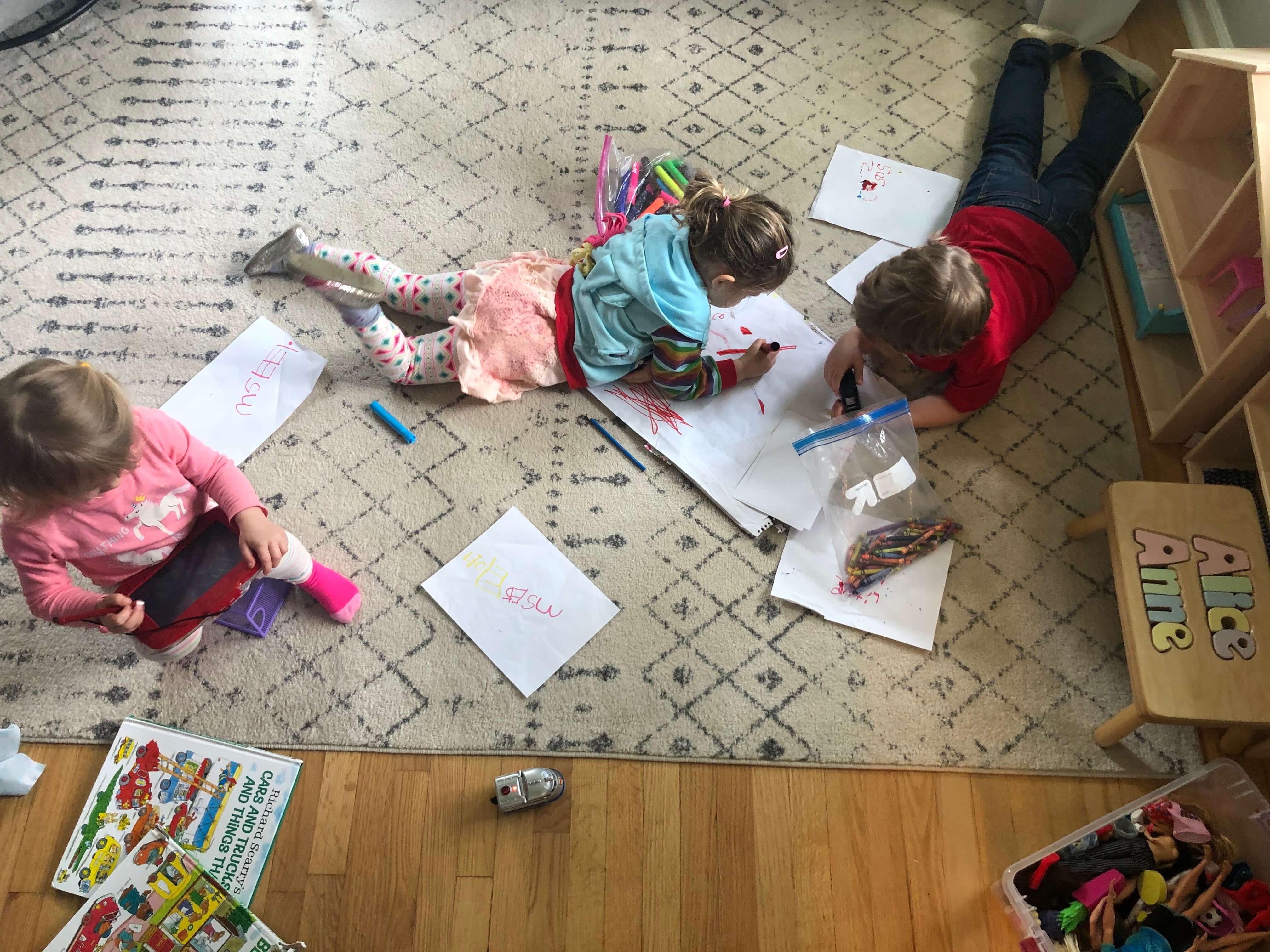Three kids doing projects on the floor