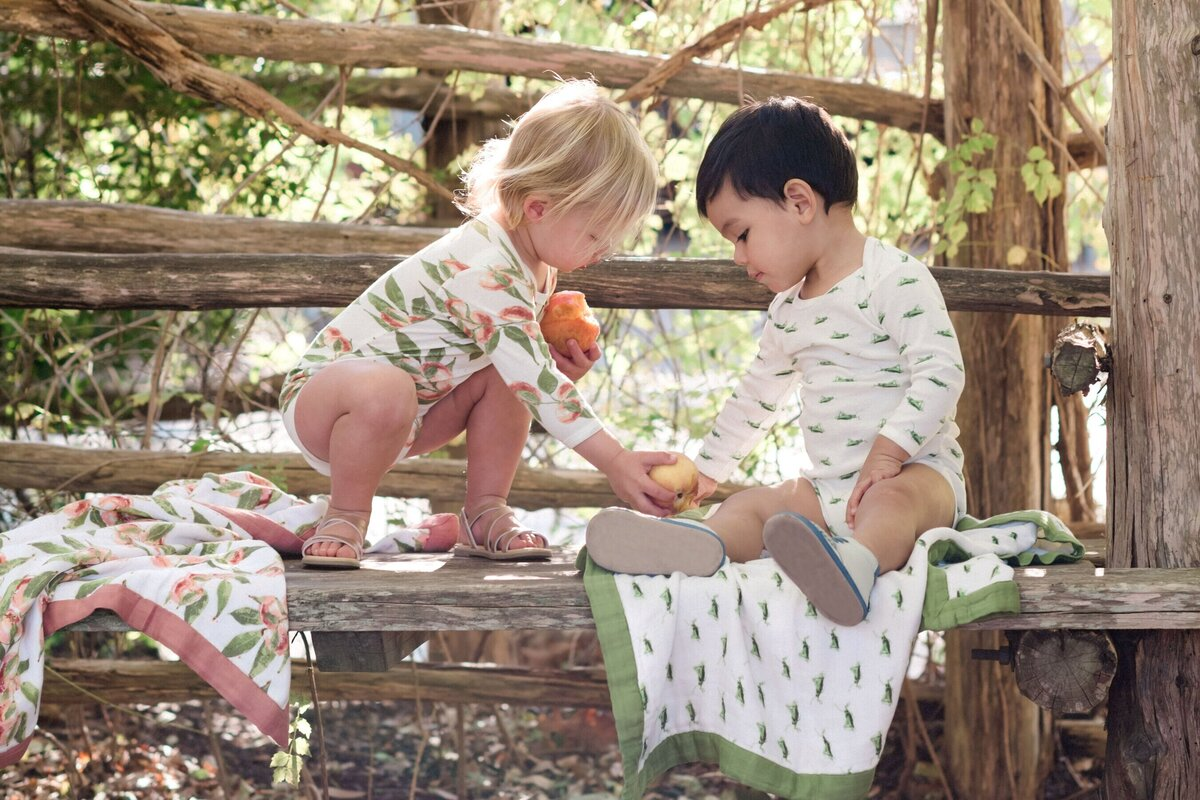 Lifestyle photo of two toddlers wearing MilkBarn kids organic cotton bodysuits (one in peaches and one in grasshopper) sharing a peach with Big Lovey Blankets from MilkBarn Kids by them on a wooden bench