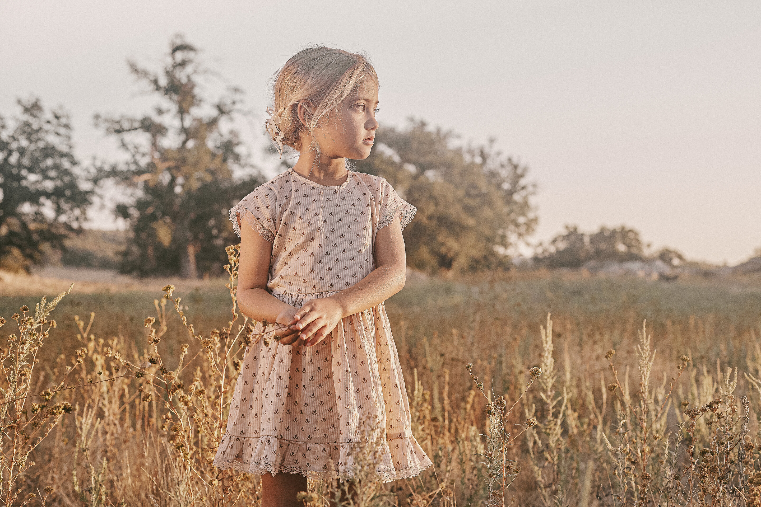 Lifestyle photo of little girl in vintage-inspired dress standing in field for new brand Noralee dresses by designer of Rylee + Cru - photo used on Barn Chic Boutique Instagram links page