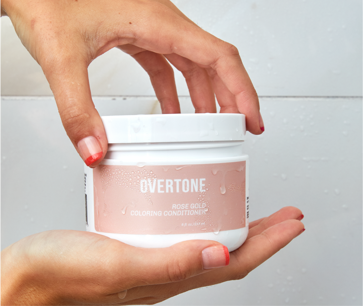 image of hands holding rose gold coloring conditioner